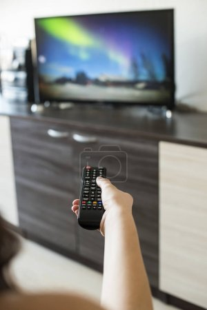 Hand hold TV remote control. TV on the background.