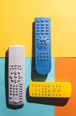 Many Colored TV remote controls on bright backgrounds.