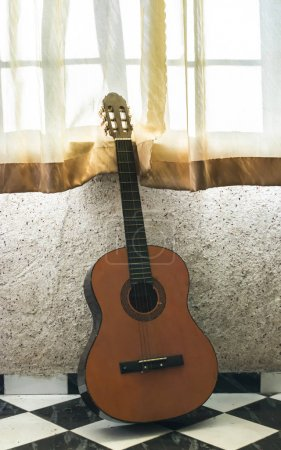 An old guitar to the window on background