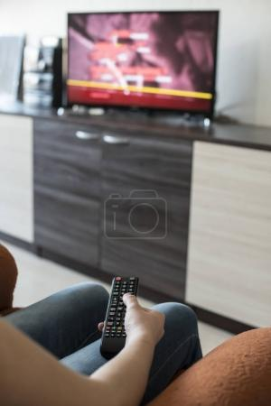 Woman hold TV remote control. TV on the background.