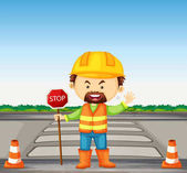 Road worker holding stop sign on the road