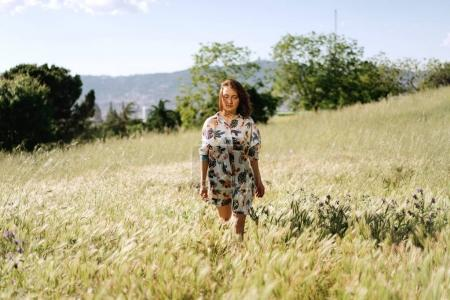 Beautiful caucasian female is enjoying the windy and warm sunny day while walking amidst the field. Young stylish woman with brown hair wearing a colorful dress is relaxing outdoors on a summer day.