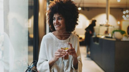 Half length portrait of beautiful afro-american female with afro hair style in casual clothes smiling aside while enjoying relaxing herbal tea in a modern coffee shop on a weekend.