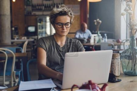 Young caucasian female is banking online while sitting in a cafe with a portable computer connected to a public wi-fi. Entrepreneur female is working on a laptop while having brunch in a cafe.