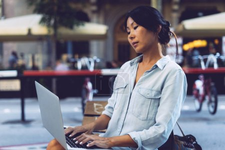 Beautiful asian female is sitting at city cafe with a laptop connected to wi-fi. Young entrepreneur is working on a portable computer while sitting outdoors on a blurred urban background.