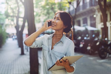 Photo for Asian entrepreneur female is having call by a mobile phone while standing with a laptop in her hand on a blurred urban background. Cute student girl is going down the street holding digital devices. - Royalty Free Image