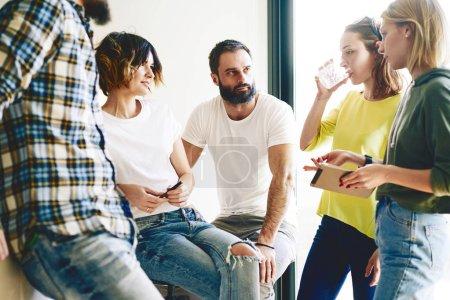 Photo pour Équipe de professionnels jeunes et réussies discutent les idées de business. Groupe de jeunes gens modernes dans une tenue décontractée est d'avoir une séance de remue-méninges en l'espace de coworking moderne. - image libre de droit