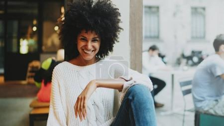 Photo for Half length portrait of a cheerful mulatto female with afro hair style wearing stylish clothes smiling at the camera while sitting in a modern city coffee shop on a weekend day on a blurred backgrond. - Royalty Free Image