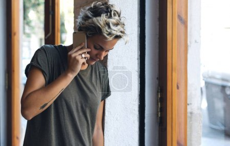 Young beautiful caucasian woman with blonde hair is talking by a smartphone while standing beside the window. Hipster girl in a khaki t-shirt is chatting with friends by a mobile phone.