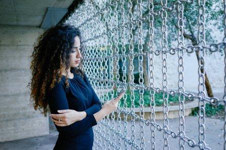 Photo pour Jeune femme attirante avec smartphone dans un contexte de bâtiment modern contemporain - image libre de droit