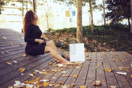 Photo pour Belle jeune femme aux cheveux long bouclés faire des achats en ligne pendant la pause déjeuner assis dans le parc avec sac en papier blanc blanc debout à côté d'elle - image libre de droit