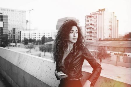 Photo pour Portrait de la belle jeune femme brune à l'aide de smartphone sur un fond de bâtiments de ville - image libre de droit
