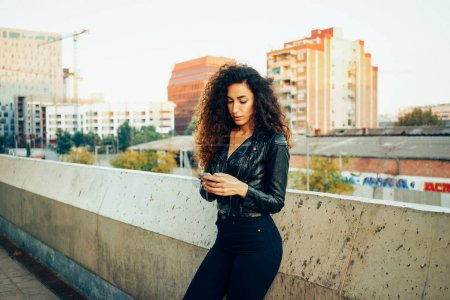Photo for Portrait of beautiful brunette young woman using smartphone on a city buildings background - Royalty Free Image