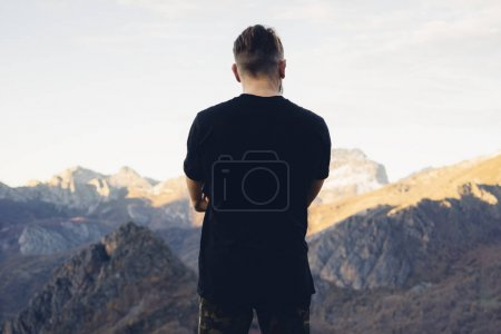 Photo for Young hipster man wearing a black blank t-shirt on the mountain background. Back view - Royalty Free Image