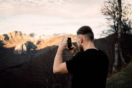handsome young man taking pictures of beautiful mountains during sunset