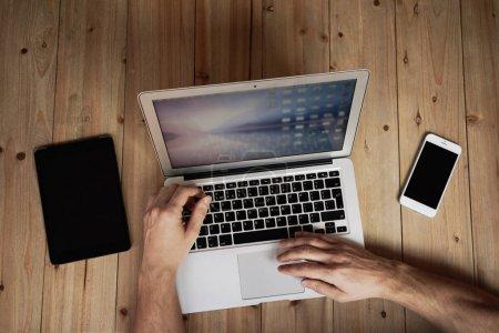 Photo pour Image recadrée de mains masculines tapant sur le clavier de l'ordinateur portable au bureau à domicile - image libre de droit