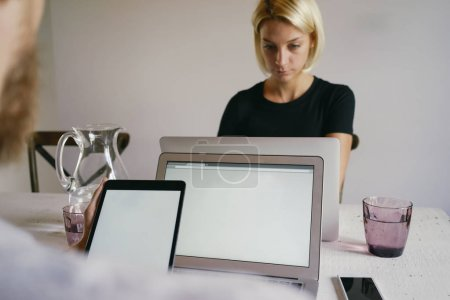 Man typing on laptop against young women and using digital tablet with blank empty screen