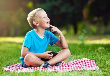 Cute boy in a park thinking
