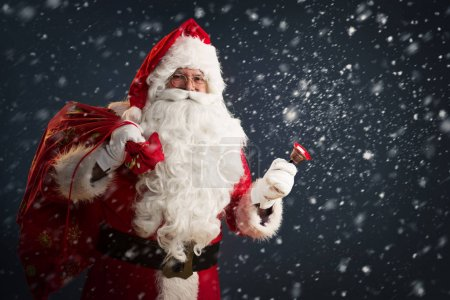 Photo for Santa Claus with sack and bell  on dark  background - Royalty Free Image