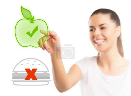 Photo for Beautiful woman choosing between healthy and unhealthy food - Royalty Free Image