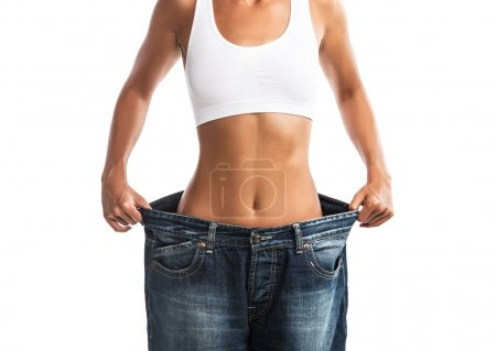 Fit, beautiful, young woman in oversize pants close up, isolated on white background