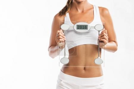 Close up of woman's abdomen, woman holding a weight scale with a year 2018 written on it - New Years weigh t loss resolution