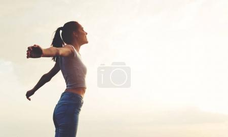 Young woman enjoying outdoors, sky background