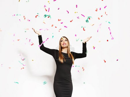 Photo for Young woman celebrating, confetti falling - Royalty Free Image