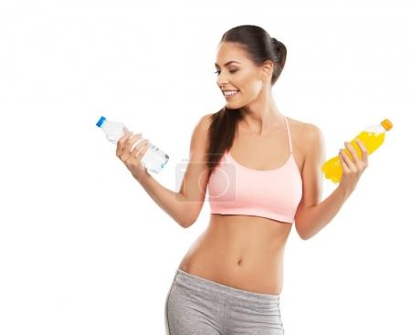 Fit young woman choosing between water and soda