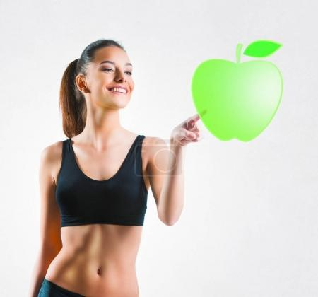Beautiful fit woman pressing a green apple symbol