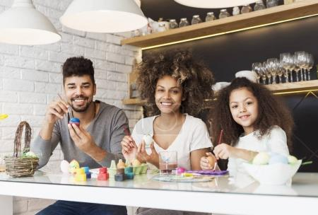 Happy African American family coloring Easter eggs
