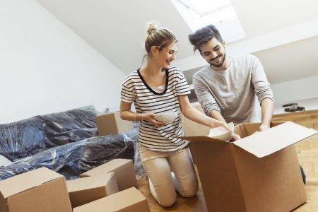 Photo for Young couple moving into their new home unpacking boxes - Royalty Free Image