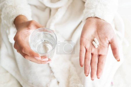 Woman holding a glass of water and pills, detail