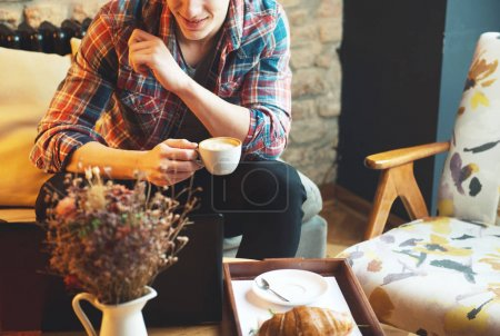 Young man sitting at a cafe, using a tablet, drinking coffee