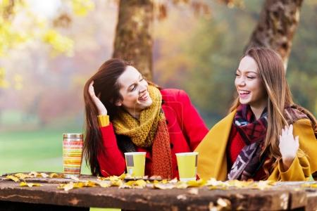 Two beautiful young women talking and enjoying drinks on a sunny autumn day