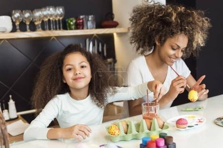 Beautiful African American woman and her daughter coloring Easter eggs in the kitchen