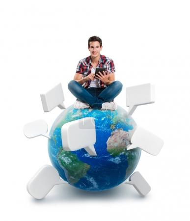 Young man sitting on a planet with a tablet. Elements of this image furnished by NASA