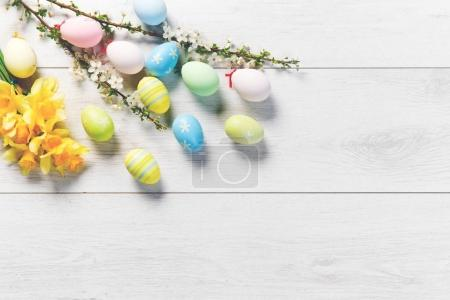 Colored eggs on a white wooden table, Easter background
