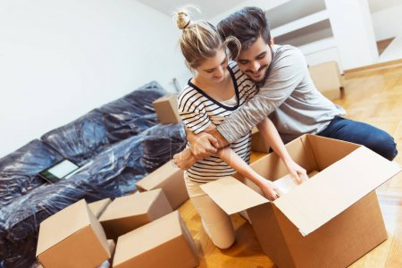 Young couple moving into their new home unpacking boxes