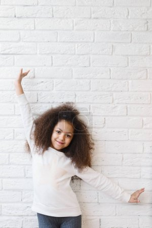 Cute girl over a white brick wall smiling