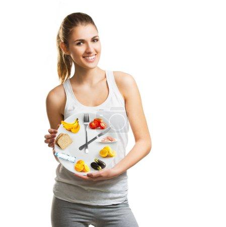 Photo pour Belle jeune femme tenant une assiette avec nourriture, régime et concept de temps - image libre de droit