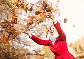 Happy, young woman throwing autumn leaves