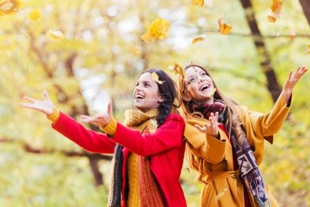 Two beautiful young women throwing leaves in a park, enjoying