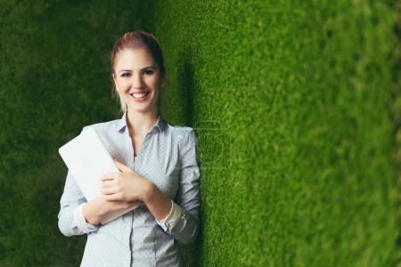 Beautiful woman standing over a green grass wall, holding a tablet