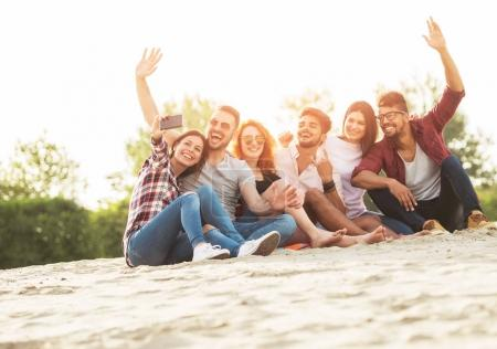Young men and women having fun outdoors on the beach taking selfie