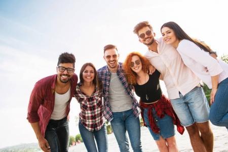 Photo pour Jeunes hommes et femmes qui s'amusent à l'extérieur sur la plage - image libre de droit
