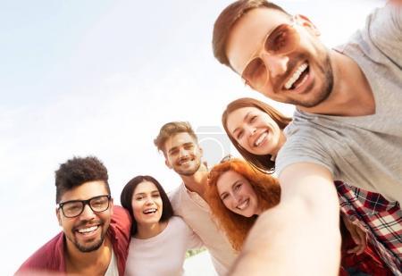 Photo pour Groupe de jeunes debout en cercle, à l'extérieur, faisant un selfie - image libre de droit