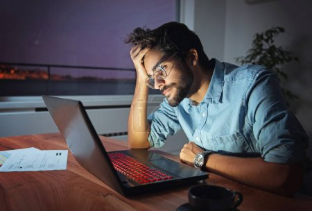 Businessman working on a laptop, overworking, under pressure, tired and sleepy
