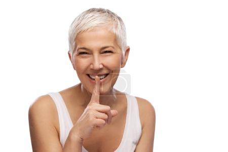 Portrait of a beautiful elderly woman showing silence gesture, smiling, isolated on white background