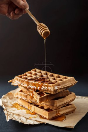 Photo for Hand pouring honey on delicious waffles - Royalty Free Image